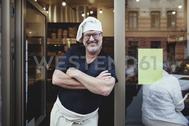 Smiling male baker standing with arms crossed at entrance of bakery - MASF00085 - Maskot/Westend61