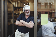 Smiling male baker standing with arms crossed at entrance of bakery - MASF00085