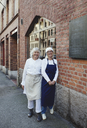 Portrait of smiling female bakers standing by brick wall outside bakery - MASF00097
