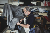 Senior male owner cutting gray fabric while standing at workshop - MASF00106