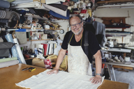 Portrait of smiling male owner standing with fabric at workbench - MASF00112