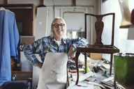 Portrait of smiling female standing by wooden chair at workbench - MASF00121