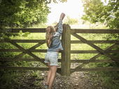 Full length rear view of girl closing wooden gate - MASF00127