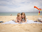 Siblings sharing smart phone while lying on towel at beach against sky - MASF00136