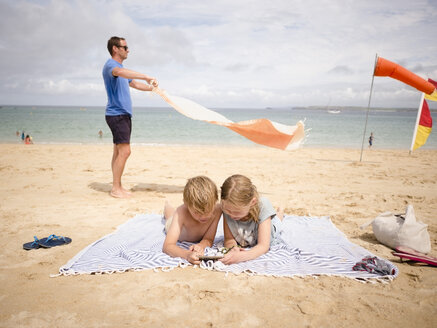 Man holding towel while children sharing smart phone at beach against sky - MASF00139