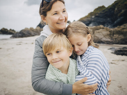 Smiling woman embracing kids standing at beach - MASF00145