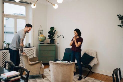 Full length of man and woman arranging sofa in living room - MASF00151