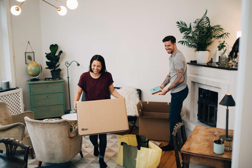 Happy couple unpacking boxes in living room at new home - MASF00154