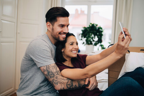 Happy couple taking selfie on mobile phone while resting in bedroom - MASF00157