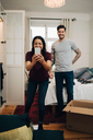Woman taking selfie on mobile phone while standing with man in bedroom - MASF00166