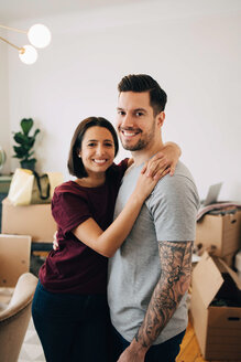 Portrait of smiling couple embracing while standing in living room during relocation - MASF00181