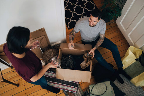 High angle view of man and woman unpacking box in living room - MASF00196