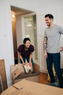 Couple enjoying while unpacking boxes in new apartment - MASF00199