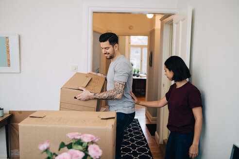 Woman standing by man carrying cardboard box in living room - MASF00202