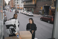 Male and female workers are stacking cardboard boxes in delivery van - MASF00235