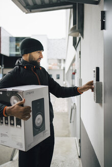Serious male worker ringing intercom while carrying box during delivery - MASF00238
