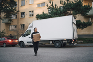 Full length of female worker carrying box while walking against delivery van on street - MASF00247