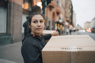 Thoughtful woman carrying box while walking with coworker in city during delivery - MASF00250