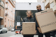 Portrait of male and female messengers carrying cardboard boxes while standing against delivery van in city - MASF00256