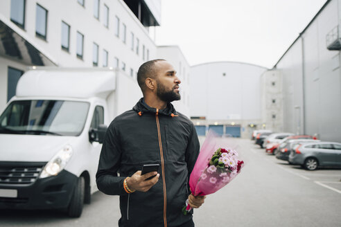 Male worker with bouquet of flower and smart phone searching in city - MASF00277