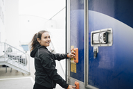 Smiling woman pushing buttons on delivery van - MASF00280