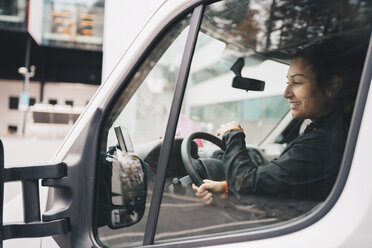 Smiling woman driving delivery van in city - MASF00286