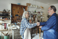 Senior owner shaking hands with customer while selling wooden chair at workshop - MASF00292