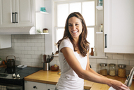 Happy woman looking away while washing dish in kitchen at home - CAVF34575