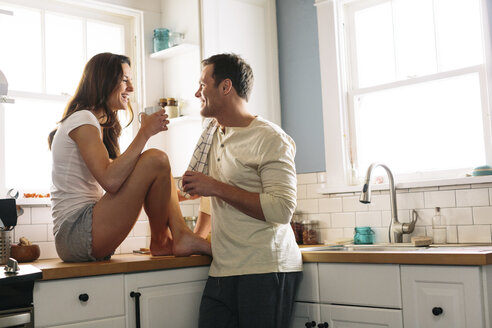 Happy couple having coffee in kitchen at home - CAVF34578