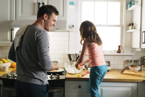 Happy father and daughter preparing food in kitchen at home - CAVF34626