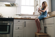 Smiling girl rubbing hands with napkin while sitting on kitchen counter at home - CAVF34629