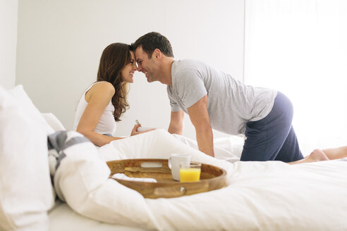 Side view of happy couple face to face in bed at home - CAVF34635