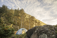 Low angle view of tents on mountain against cloudy sky - CAVF34665