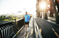 Man running while exercising on bridge against clear sky in city - CAVF34674
