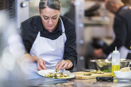 Female chef garnishing food while coworker working in background at restaurant - CAVF34701