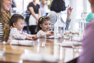 Family sitting at table in restaurant - CAVF34713