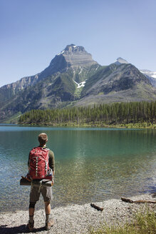 Rear view of man with backpack standing on lakeshore at Glacier National Park - CAVF34911