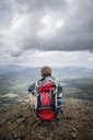 Rear view of hiker with backpack sitting on mountain against cloudy sky - CAVF34932