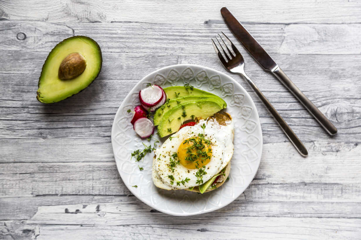 Toast with with fried egg, avocado, red radish, tomato and cress - SARF03655 - Sandra Roesch/Westend61