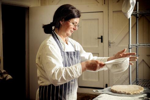 Female baker sprinkling flour on bread dough at bakery - CAVF35025