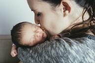 Close-up of woman kissing baby girl at home - CAVF35067
