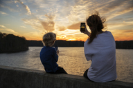 Boy and girl sitting on ledge photographing sunset - CAVF35094