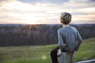Boy looking at sunset sitting on fence - CAVF35109