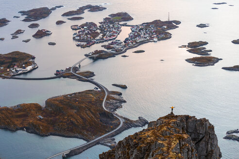 Norway, Lofoten Islands, Henningsvaer, man standing on viewing point with raising arms - WVF00995