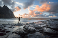 Norway, Lofoten Islands, man with raised arms at Kvalvika Beach in the evening - WVF01022