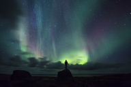 Norway, Lofoten Islands, Eggum, man standing on rock and watching northern lights - WVF01025