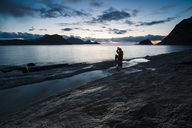 Norway, Lofoten Islands, Haukland Beach, man sitting on rock, building heart with fingers - WVF01038