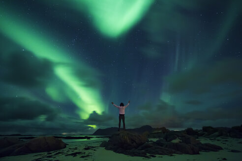 Norway, Lofoten Islands, Eggum, northern lights, young man with raised arms - WVF01044