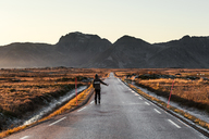 Norway, Lofoten Islands, back view of man hitchhiking at empty country road - WVF01071