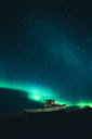 Norway, Lofoten Islands, Eggum, fishing boat under starry sky and Nothern lights - WVF01080